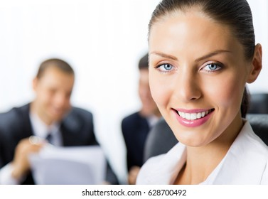 Portrait of happy smiling young businesswoman and colleagues on background, at office. Success in business and teamwork concept.