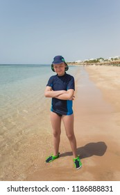 Portrait of happy smiling young caucasian tanned kid standing on sunny sandy beach in Egypt. Vertical color photo of boy in full length. Child wearing special swimwear for protection from sunlight.