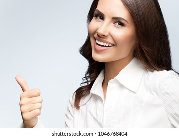 Portrait of happy smiling young cheerful businesswoman, showing thumb up hand sign gesture, on grey background. Success in business concept studio shot.