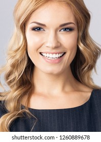 Portrait of happy smiling young cheerful business woman, on gray background