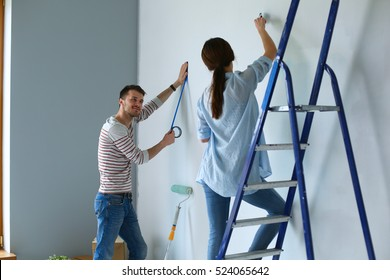 Portrait of happy smiling young couple painting interior wall new house