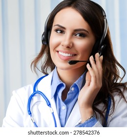Portrait of happy smiling young doctor in headset, at office