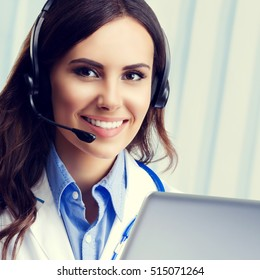 Portrait of happy smiling young doctor in headset, using laptop, with blank copyspace area for slogan or text. Healthcare, medical, online help, lab consulting and exam concept.