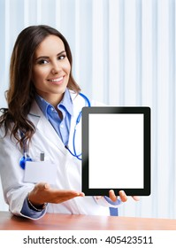 Portrait of happy smiling young female doctor showing no-name tablet pc with blank copyspace area for slogan or text, at office.