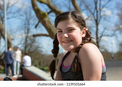 Portrait of a happy, smiling young girl with plaits in a park dressed in sporty clothes with teenage boys defocused behind in Winchester, Hampshire, UK