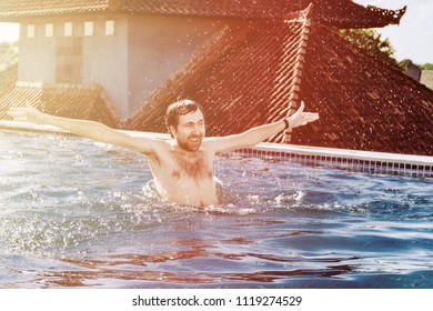 Portrait of happy smiling young man with hands up, in rooftop pool, water splashes,  day lit by the sun.