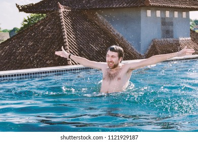 Portrait of happy smiling young man with hands up, which is bathed in pool on roof.  Emotions - excited, positive, gleeful, glad.
