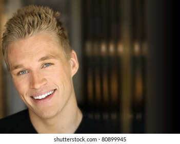 Portrait of a happy smiling young man against dark modern background
