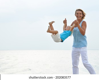Portrait of happy smiling young mother with little child playing on the beach.