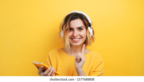Portrait of happy smiling young sexy girl in white headphones looking for good music in a smartphone, finds, dancing on isolated yellow background. Pleasure. Emotions of people. Monotone. Copy space