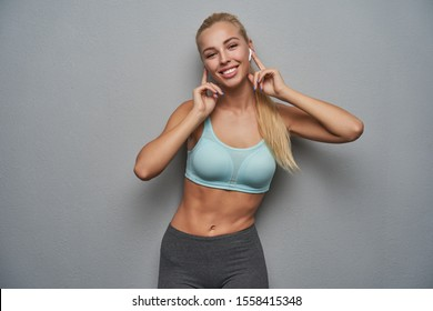 Portrait of happy smiling young slim lady with ponytail hairstyle holding index fingers on earphones while standing over grey background, being in high spirit and listening to music
