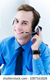 Portrait of happy smiling young support phone male operator in headset, at workplace. Help service and client consulting call center concept.