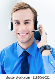 Portrait of happy smiling young support phone male operator in headset, blue shirt and tie, at workplace. Help service and client consulting call center concept.