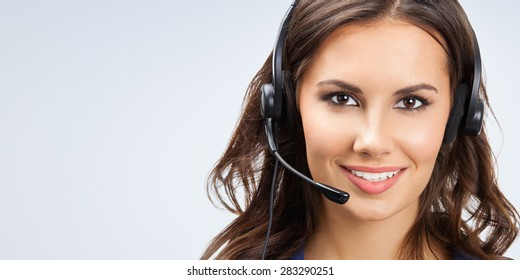 Portrait of happy smiling young support phone operator or businesswomen in headset, with blank copyspace area for slogan or text
