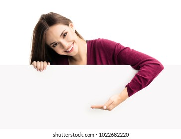 Portrait of happy smiling young woman in red casual smart clothing, showing empty blank signboard with copyspace area for text or slogan, isolated against white background