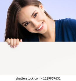 Portrait of happy smiling young woman in blue casual smart clothing, showing empty blank signboard with copyspace area for text or slogan, over violet background