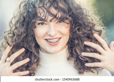 Portrait of a happy smiling young woman with dental braces and and curly hair.