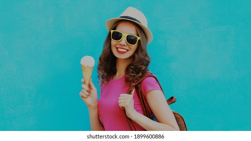 Portrait of happy smiling young woman with ice cream wearing a summer straw hat on a blue background