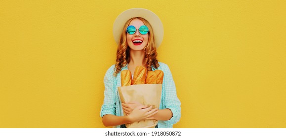 Portrait of happy smiling young woman holding grocery shopping paper bag with long white bread baguette on a yellow background