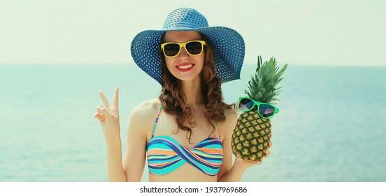 Porträt einer glücklichen, lächelnden jungen Frau am Strand mit lustigen Ananas mit einem Strohhut