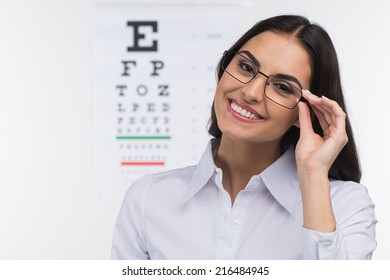 Portrait of happy smiling young woman. girl holding glasses in eye doctor, isolated over white background