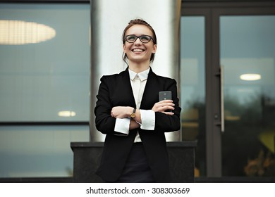 Portrait of happy smilling business woman with smartphone. Success manager woman on still office background, looking on the sky and success future.
