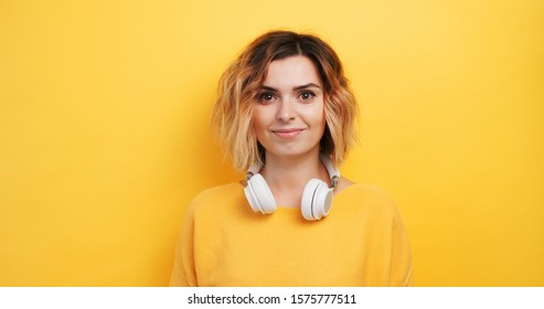 Portrait happy smily young sexy girl  listening to music in white headphones on an isolated yellow background. Pleasure. The emotions of people. Monotone. Copy space