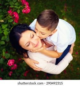 portrait of happy son kisses mother in spring garden, top view
