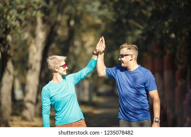Portrait of happy sporting man and woman doing handshake on morning jog