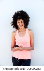 Portrait of happy sporty woman with headphones holding mobile phone