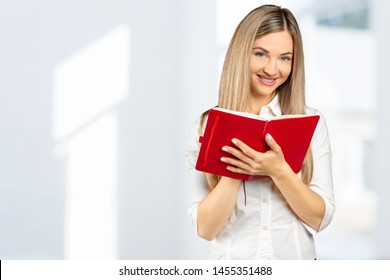 Portrait of a happy student girl or woman with books in library