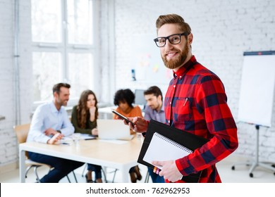 Portrait of happy student standing at university classroom with colleagues in background