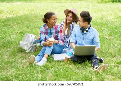 Portrait of happy students sitting on green lawn with laptop chatting and smiling enjoying break on summer day