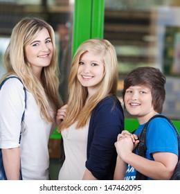Portrait of happy students standing together against door in school