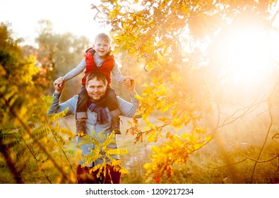 Portrait of happy stylish family on autumn walk. Father and child son in autumn park having fun and laughing. Family playing outdoors together. Child pilot on dads back. Travel and vacation.