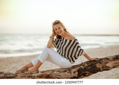 Portrait of happy stylish traveller woman in white pants and striped blouse sitting on a wooden snag on the seashore in the evening.
