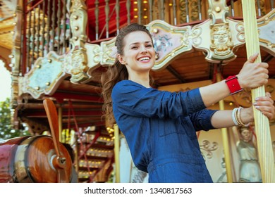 Portrait of happy stylish traveller woman in blue jeans overall riding on the carousel.
