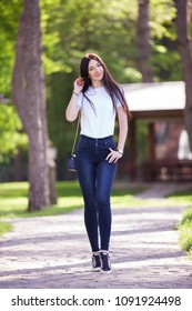 Portrait of happy stylish woman in blue jeans and white t-shirt, walking on the street. Fashion woman lifestyle. Trendy outfit. Beauty nature scene with colorful background at spring or summer time