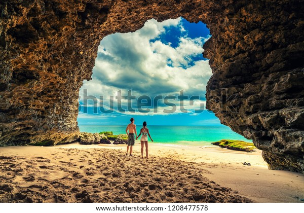 Portrait of happy successful couple, embracing in the Cave at the beach, sea view. Traveling at Bali. Honeymoon summer travel at Indonesia.