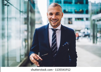 Portrait of happy successful owner of financial company dressed in stylish formal wear smiling at camera.Prosperous young businessman in elegant expensive suit standing in downtown
