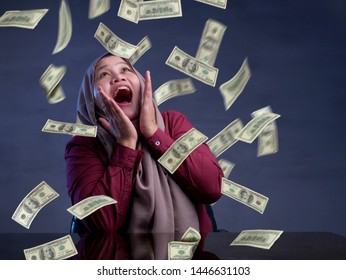 Portrait of happy successful young Asian billionaire muslim woman smiling happily under rain of money. Wealth investment economic concept