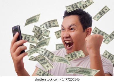 Portrait of happy successful young Asian billionaire man smiling happily under rain of money from his phone. Wealth investment internet online business concept