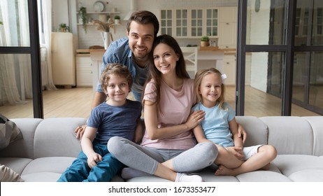 Portrait of happy successful young family with children first time home buyers sit on comfortable couch, smiling parents and little kids relax in living room look at camera posing, ownership concept