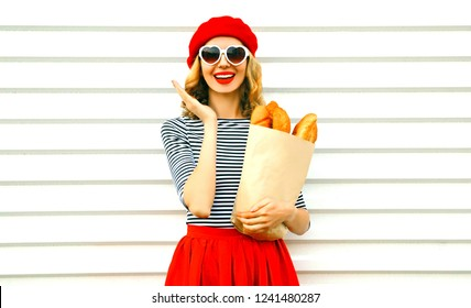 Portrait happy surprised laughing woman wearing red beret holding paper bag with long white bread baguette on white wall background