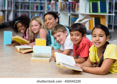 Portrait of happy teacher with children lying down while reading books in library