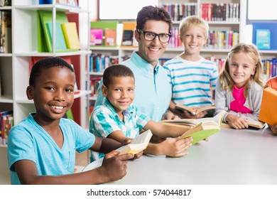 Portrait of happy teacher and kids in library at school