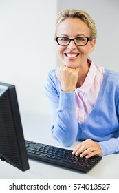 Portrait of happy teacher working on computer in classroom at school