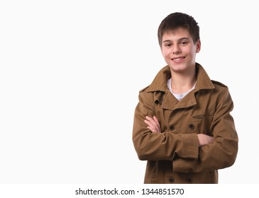 Portrait of happy teen boy with folded hands on white background. A boy with a joyful face looks straight into the camera.