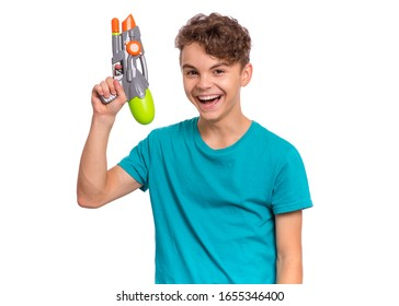 Portrait of happy teen boy playing with plastic water gun, isolated on white background. Beautiful caucasian teenager having fun with children toy. Funny summer games with water.