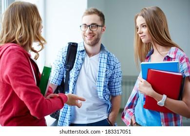 Portrait of happy teen friends talking during break in college